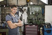 pic of grease  - Garage worker or mechanic standing in front of his tools in a garage - JPG