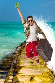 image of stereotype  - a young attractive male in a colorful outfit in a tropical island setting as a stereotype tourist - JPG
