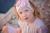 stock photo of headband  - cute curly blue eyed child girl portrait in pink flower headband - JPG