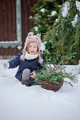 stock photo of snowy owl  - adorable happy child girl in owl hat plays with basket of fir branches in winter snowy garden - JPG