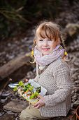 stock photo of early spring  - adorable happy child girl with pigtails holding egg box with herbs in early spring garden - JPG