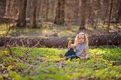 image of early spring  - adorable smiling blonde child girl plays in green plants on the walk in early spring forest - JPG