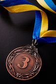 stock photo of medal  - Bronze medal in the foreground on yellow blue ribbon - JPG