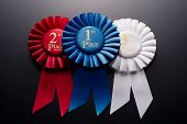 image of rosettes  - 1st 2nd and 3rd place pleated ribbon rosette on a dark background - JPG
