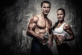 picture of dumbbell  - Athletic man and woman with a dumbbells - JPG