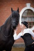 image of horse girl  - Portrait of the girl and black horse. The girl communicates with a beautiful horse. Equestrian sport.
