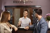 picture of receptionist  - Portrait of happy female receptionist giving information to young couple - JPG