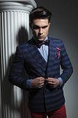 stock photo of down jacket  - Smart casual fashion man looking down while closing his jacket - JPG