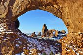 foto of arch  - Turret Arch seen through North Window Arch in Arches National Park Utah in winter - JPG
