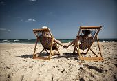 stock photo of couple sitting beach  - Couple sitting in beach chairs and holding hands on a tropical beach - JPG