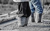 image of concrete  - Concrete workers in heavy boots working in new wet concrete - JPG