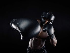 image of boxers  - Portrait of african male practicing boxing against black background - JPG
