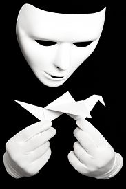 foto of shadoof  - White theatrical mask and paper japanese crane isolated on black - JPG