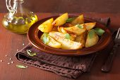 stock photo of baked potato  - baked potato wedges in plate over brown rustic table - JPG
