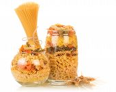 image of glass noodles  - Raw italian pasta in glass bottles on white background table - JPG