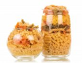 picture of glass noodles  - Uncooked italian pasta in glass bottles on white background table - JPG
