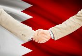 picture of bahrain  - Businessmen shaking hands with flag on background  - JPG