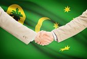 pic of coco  - Businessmen shaking hands with flag on background  - JPG