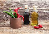 stock photo of vinegar  - Olive oil and vinegar in glass bottles chilly pepper on wooden background - JPG