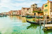 stock photo of gondola  - Beautiful colorful image of a canal in Venice with moorings and a gondola in the forefront and old houses under blue cloudy sky in the background - JPG
