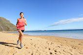 stock photo of biracial  - Jogging sports athlete runner woman running on beach sweating - JPG