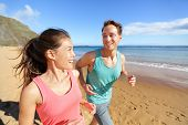 foto of cardio exercise  - Young couple talking running on beach jogging - JPG