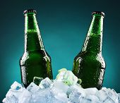 image of ice cube  - Glass bottles of beer in ice cubes on color background - JPG