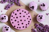 image of berries  - Traditional purple berry cupcakes with souffle dessert decorated with fresh berries on white kitchen table background - JPG