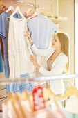 stock photo of pullovers  - Elegant girl looking for new pullover in clothing department - JPG