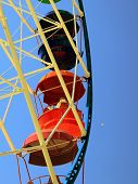 image of amusement park rides  - ride a Ferris wheel at an amusement park against the blue sky - JPG