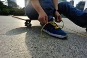 picture of skate board  - young skateboarder tying shoelace at skate park - JPG