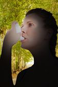 picture of asthma  - Woman using inhaler for asthma against walkway along lined trees in the park - JPG