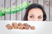 picture of peek  - Pretty brunette peeking at chocolate against wooden planks - JPG
