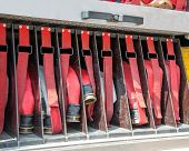 stock photo of fire brigade  - aprons and red water pipes in fire trucks to fire off - JPG