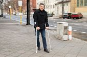 stock photo of crutch  - Portrait Of A Man Trying To Walk On Street With The Help Crutches - JPG