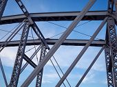 pic of girder  - Detail shot of an historic gray painted Dutch riveted truss bridge against a blue sky - JPG