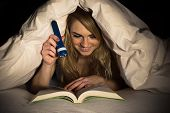 picture of torches  - Young Woman Under Bedding Reading Book Holding Torch - JPG
