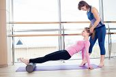 image of senior class  - Aerobics Pilates personal trainer helping women group in a gym class - JPG