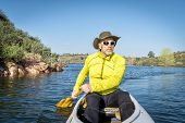 stock photo of horsetooth reservoir  - senior male paddling a decked expedition canoe on Horsetooth Reservoir - JPG