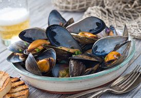 picture of shell-fishes  - A bowl of delicious steamed mussels with grilled bread and beer on a rustic tabletop with fish net - JPG