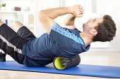 Man Lying On A Foam Roller While Doing An Exercise poster