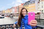 Asian tourist woman taking selfie at Copenhagen Nyhavn. Famous landmark, northern Europe destination poster