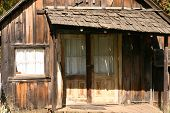 stock photo of sag  - a rustic shack that has a porch roof sagging - JPG