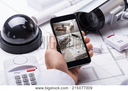 poster of Person Hand Using Home Security System On Mobilephone With On Blueprint With Security Equipment