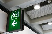 Fire Exit Sign Lightbox In The Airport Terminal Emergency Exit Way. Green Emergency Exit Sign Direct poster