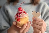 Woman holding wooden heart and tasty cupcake for Valentines Day poster