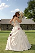 foto of top-hat  - A bride standing on grass holding a hat - JPG