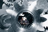 Industry-workers, engineers standing inside a giant steel shaft, steel industrial concept poster