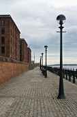 Cobbled Paved Footpath Walkway Promenade Enbankment Along Old Red Brick Historic Buildings At Liverp poster