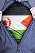stock photo of saharan  - A Western Saharan businessman rips open his shirt and shows how patriotic he is by revealing his countries flag beneath printed on a t - JPG